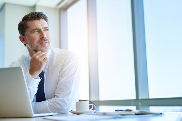 Arbeitsrecht Arbeitgeber am Schreibtisch schaut aus dem Fenster