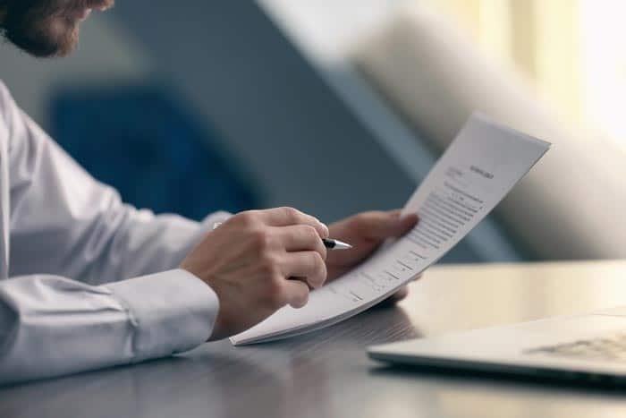 Arbeitsrecht Mann kontrolliert seinen Arbeitsvertrag