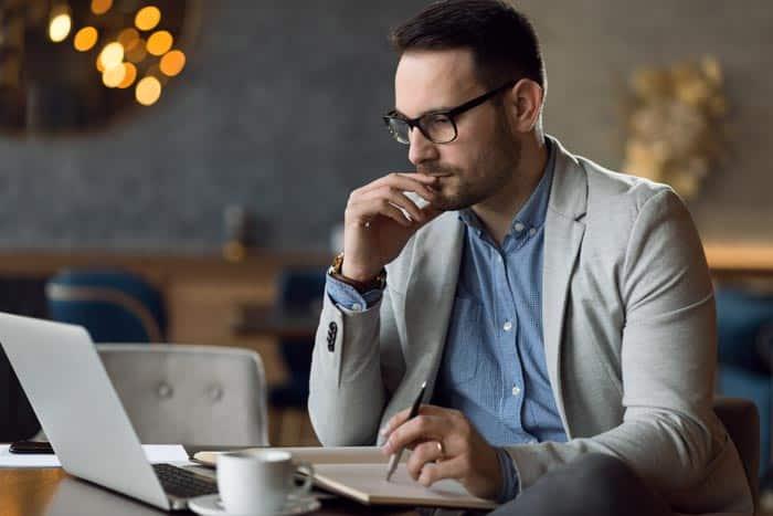 Forderungsbeitreibung Geschäftsmann am Schreibtisch vor einem Laptop