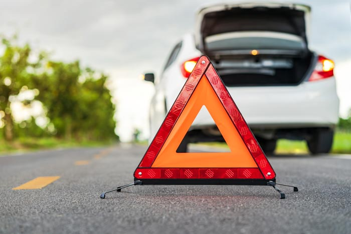 Unfallrecht Warndreieck vor einem weißen Auto