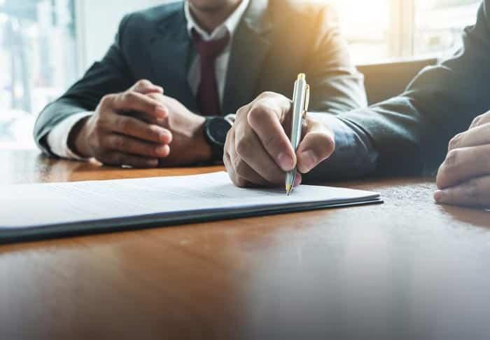 Vertragsrecht Ein Mann unterschreibt einen Vertrag